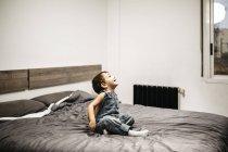 Niño sentado en la cama de sus padres viendo algo - foto de stock