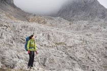 Mountaineer walking in mountainscape at daytime — Stock Photo