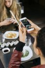 Woman taking picture of sushi in restaurant with friend on background — Stock Photo