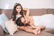 Teenage girl and her little sister lying on couch — Stock Photo