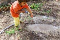 Мальчик поливает сад садовым шлангом — стоковое фото