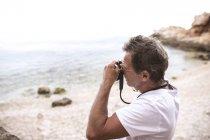 Senior man taking picture on the beach — Stock Photo