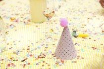 Sombrero de fiesta y soplador de fiesta en la mesa con confeti - foto de stock