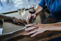 Primo piano di una coppia detenzione mani in ristorante — Foto stock
