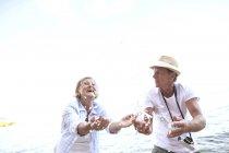 Активні милий старший пара бризки води на пляжі — стокове фото