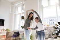 Красива кавказька брюнетка жінка танці з дочкою на дому — стокове фото