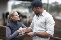 Couple of woman and man with clipboard on farm — Stock Photo