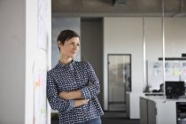 Businesswoman standing in office with arms crossed and thinking — Stock Photo