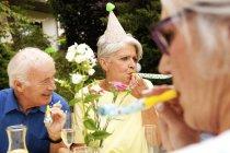 Adultos mayores celebran la fiesta de cumpleaños en el jardín - foto de stock