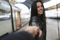 Jovem feliz de mãos dadas na estação de trem — Fotografia de Stock