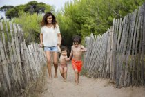 Happy mother and two children walking hand in hand on beach path — Stock Photo