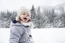 Girl in winter landscape catching snowflakes with her tongue — Stock Photo