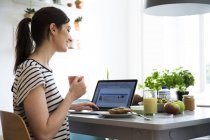 Beautiful caucasian brunette woman working on laptop at home — Stock Photo