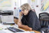 Maturo uomo telefonare a scrivania in ufficio — Foto stock