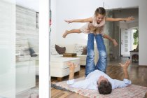 Father balancing his daughter on his feet — Stock Photo