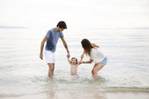 Parents playing in the sea with their little girl — Stock Photo