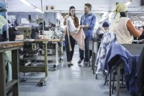 Designers in factory discussing dress while seamstresses at desks in factory sewing clothes — Stock Photo