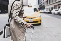 Woman standing at the roadside with mobile phone and suitcase, New York City, USA — Stock Photo