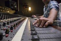 Mão de um homem que trabalha na sala de controle de um estúdio de gravação — Fotografia de Stock