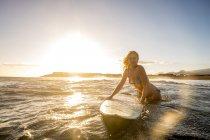 Испания, Тенерифе, молодая серфингистка в море на закате — стоковое фото