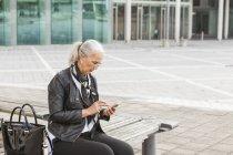Mulher madura na moda sentada no banco usando telefone celular — Fotografia de Stock