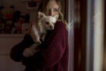 Женщина, глядя через окно с собакой на руках — стоковое фото
