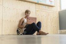 Blonde attrayante femme d'affaires en utilisant un ordinateur portable sur le sol — Photo de stock