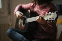 Young woman playing guitar at home — Stock Photo