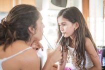 Teenage girl and her little sister in kitchen sharing a drink — Stock Photo
