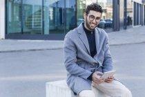 Retrato de sonriente joven con mini tablet sentado en pivote - foto de stock
