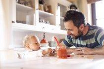 Padre y bebé en casa en la mesa de comedor - foto de stock