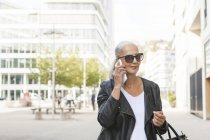 Portrait of smiling woman wearing sunglasses and leather jacket on the phone — Stock Photo