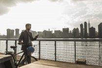 Homme d'affaires à vélo marchant le long d'East River et utilisant un téléphone portable, New York, États-Unis — Photo de stock