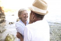 Active cute senior couple hugging outdoors — Stock Photo