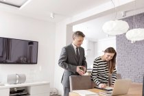 Бизнесмен и женщина, подписание документа в гостиной — стоковое фото