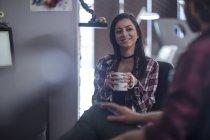 Mulher sorridente com caneca de café em uma reunião — Fotografia de Stock