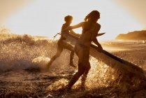 Surfers працює в море на заході сонця — стокове фото