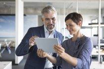 Бизнесмен и предпринимательница вместе пользуются планшетом в офисе — стоковое фото