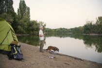 Senior man with dog camping at a lake — Stock Photo