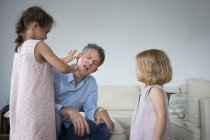 Daughter sticking band aid on father cheek — Stock Photo