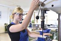 Weiblichen Auszubildenden arbeiten bei Presse-Bohrer — Stockfoto