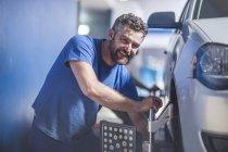 Meccanico auto sorridente sul lavoro in officina — Foto stock