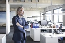 Businessman standing in office with arms crossed and thinking — Stock Photo