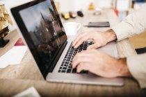 Человек сидел на своем столе, используя ноутбук — стоковое фото