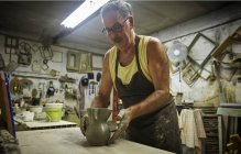 Potter in workshop placing earthenware jug on table before kilning — Stock Photo