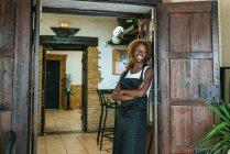 Smiling young waitress at the door of a bar — Stock Photo