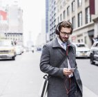 Businessman with cell phone and headphones on the go, New York City, USA — Stock Photo