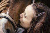 Giovane donna baciare cavallo marrone — Foto stock
