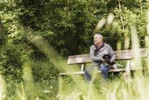 Sonriente a hombre mayor sentado con su perro en un banco en la naturaleza - foto de stock
