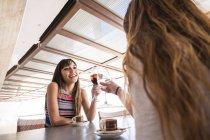 Due amiche donne che si accarezzano gli occhiali nel caffè — Foto stock